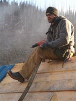 Christoph Lotter applies roofing steel to the new woodshed.
