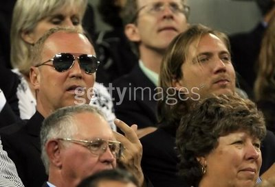 Michael Kors and Lance Le Pere, Vice President of Michael Kors Women's Design, watch the match between Amelie Mauresmo of France and Serena Williams during the U.S. Open, September 4, 2006. (Photo by Jamie Squire/Getty Images)