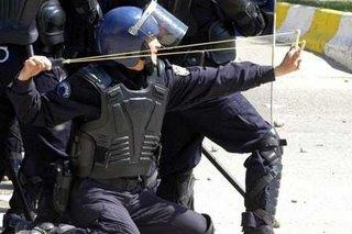Yetkileri elinden alınmış bir Türk Polisi,göstericilere sapanla müdahale ederken...