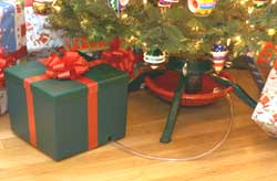 this christmas tree watering system is pretty clever it has a reservoir of water camouflaged inside a present you only have to water your tree every