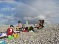 Cousins chat on the beach, with a rainbow overhead