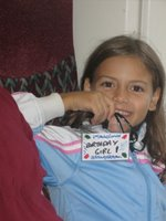 Lauren on the train to London, holding up a badge that says Birthday Girl