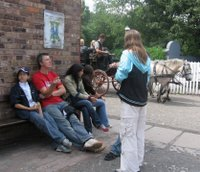 A horse drawn carriage goes past in Blists Hill