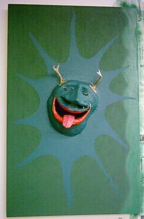 attaching paint and antlers to papier mache piece, on canvas