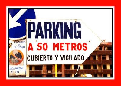 Vista general de la entrada al aparcamiento público en la Calle Vícor García de la Concha, Villaviciosa, Asturias. Detalle del anuncio de aparcamiento privado