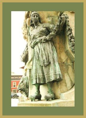 Mariano Belliure y Gil: Monumento a Obdulio Fernández (1927-1932). Detalle de una de las aldeanas en actitud de 'tirar' de la guirnalda, vestida de modo 'tradicional' al uso en la población rural de la época.