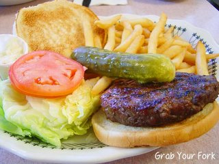 Bison burger with pickle, salad and fries