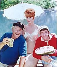 From left to right: Alan Hale, Jr as the Skipper, Tina Louise as Ginger, and Bob Denver as Gilligan