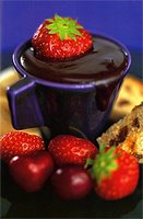 Melted chocolate in a cup with strawberries