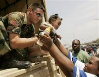 Five-month-old Heaven Girod is handed over to a National Guardsman as she is being evacuated from a flooded area in New Orleans August 30, 2006. 30 Aug 2005 REUTERS/Rick Wilking.
