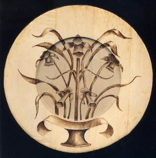 Woodburned foxglove flowers on a wood plate.