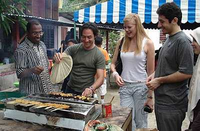 MALAYSIAN DELICACY: Ratigan trying his hand at grilling satay. With him are Dr Zambry (left), Mason and Iranian tourist Reza Khedmati.