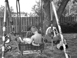 Kids on swing with toys in yard