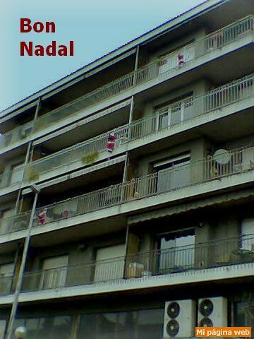 Tres muñecos trepan por la fachada de un edificio de viviendas. Feliz Navidad