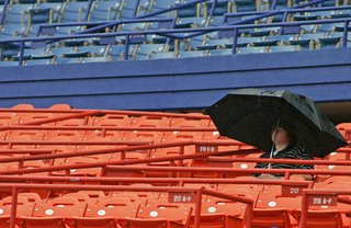 One lonely fan braves the rain delay, thousands of fans were packed onto the concourse of the field level