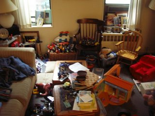 looking west: fake coffee table, windows with mess beneath, random assortment of toys, laundry and more