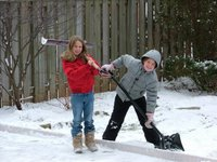 Kate and Laura shovelling the snow off the backyard rink
