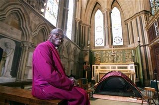 The Archbishop of York, John Sentamu, smiles after having his head shaved as part of his Sunday service at York Minster cathedral in York, northern England August 13, 2006. Image from REUTERS/Nigel Roddis