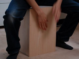 Cajon player sits on the instrument.