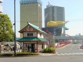 The view from Asakusa station includes a koban in the style of a shinto shrine and the 'golden turd' atop the Asahi Building in the background