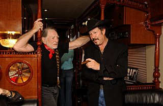 Kinky and Willie Nelson discuss renewable energy on Willie's biodiesel-powered bus. Photo by Brian Kanof.