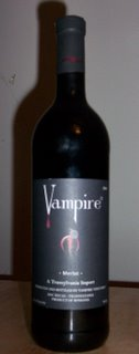Large black bottle of wine with a grey label saying Vampire, with a drop of blood dripping from the V, and a red trident symbol of some sort lower down