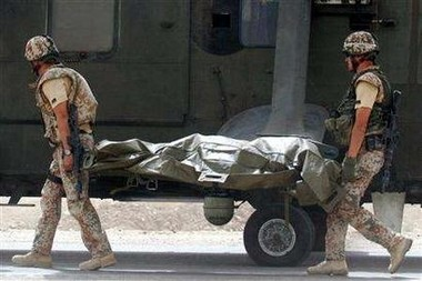 The body of one of two British soldiers killed in a roadside bomb attack near Basra September 4, 2006 being carried by two Danish soldiers