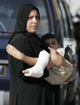 Mother carrying her injured son. The boy was wounded in the overnight rocket attacks in Baghdad August 31st 2006