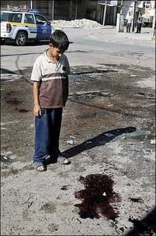 An Iraqi boy looks at a stain of blood at the site where a roadside bomb targeted an Iraqi police patrol, in central Baghdad.