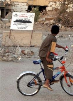 A Iraqi boy on his bicylcle looks at a warning sign in English