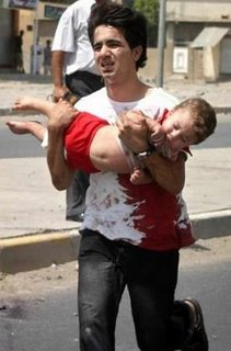 A youth runs for help carrying his wounded toddler brother after a car bomb attack in Kirk July 29th 2006