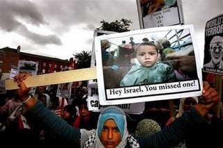 A protester holds up a sign showing a refugee child with the slogan 'Hey Israel! You Missed One' Parnell Square Dublin July 29 2006