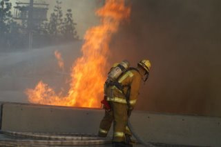 Firefighters use handlines at the parapets. Photo by Orlando Ramos - LAFirePhotos.com