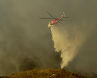 An LAFD Helicopter battles flames in the Verdugo foothills on September 3, 2005.   photo by Jim Doyle