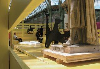 Eine Art abgeschlossener gelber Holzbühne stand im rechten Bereich der Halle rum. Darauf mischten sich alte Statuen mit neueren Kunstwerken und einer Sitzecke.