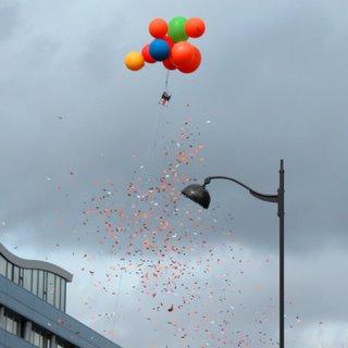 Eine Kiste mit Flugblättern wurde an vielen kleinen Ballons nach oben steigen gelassen und dann geöffnet.