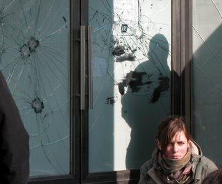 Mädchen vor zertrümmerten Glastüren und Schaufenstern