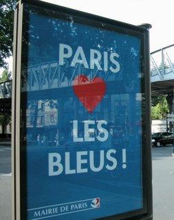 """Paris aime les bleus - Paris mag die Blauen. Auch im Parc des Princes hat sich das Rathaus, das die Veranstaltung finanziert hat, gut in Szene gesetzt und zum textlich fragwürdigen aber stimmungsmäßig bombastischen """"I will survive"""" einen """"Die Stadt Paris heißt Sie willkommen im Parc des Princes""""-Schriftzug mit Logo eingeblendet, nachdem in einem kurzen Film die Erfolgsgeschichte von Zinédine Zidane gefeiert wurde. RTL ist auf den Zug aufgesprungen und ließ nach der WM überall optisch an das hier abgebildete Plakat angelehnte Anzeigen aufhängen, die sich einfach nur """"Merci"""" lesen."""