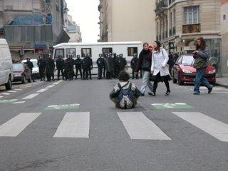 Die meisten Seitenstraßen waren mit einer dichten Reihe von Polizisten abgeriegelt. Das wurde nicht als angenehmes Symbol empfunden, auch wenn die Polizisten schon immer am anderen Ende der Straße standen. Hier demonstriert ein einzelner, indem er sich vor den Polizisten auf den Boden drängt. Beim Schießen des Fotos noch wurde ich von einem der Ordner zusammen mit anderen Fotographen wegkomplimentiert, da er sich Sorgen machte, dass ein Menschenauflauf vor der Polizei entstehen könne und das irgendwie eskalieren würde. Schade, denn ohne die beiden Fußgänger und aus einem anderen Winkel hätte das ein richtig gutes Bild werden können.