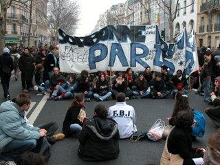 Nachdem die Demo zu Ende ist, setzen sich einige der Demonstranten mit ihrem Transparent auf den Boden zu einer Art Sit-in.