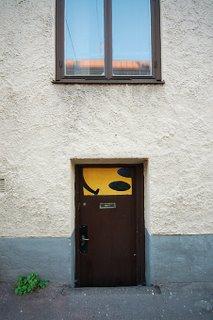 Döljer sig bakom dörren med den glada gubben en källarverkstad