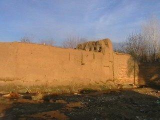 ادامه دیوار از کنار درب ورودی خانه - در انتهای بالای دیوار قسمتی از اتاقهای خانه قهرمان دیده میشود.