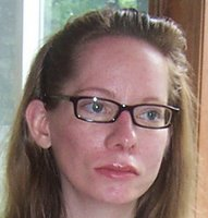 head and shoulders photo of white woman with dark-framed glasses