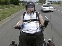 quadriplegic man using vent in his wheelchair and on a trailer behind a motorcycle cruising down an interstate highway
