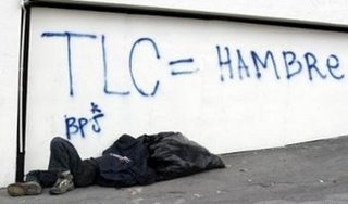 A Costa Rican homeless man sleeps under graffiti reading 'TLC = HUNGER' in San Jose, Costa Rica, Sunday, May 7, 2006. The letters TLC are the abbreviation for 'Free Trade Agreement' in Spanish. Opponents of the Free Trade Agreement between the United States and Central America plan to march tomorrow as President Elect Oscar Arias is sworn into office. (AP Photo/Kent Gilbert)