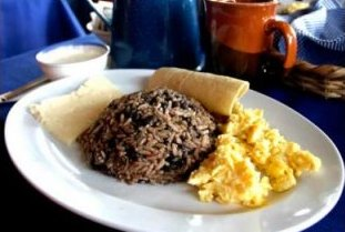A typical plate of Gallo Pinto with a side order of scrambled eggs, tortilla and a slice of cheese. A favorite Costa Rican traditional dish.