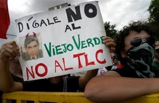 An unidentified person holds a poster reading 'Say no to the green old man, say no to the TLC (Free Trade Agreement)' and showing a photo of new President Oscar Arias during a demonstration against CAFTA and Arias's presidential inauguration on Monday May 8, 2006 in San Jose, Costa Rica near the National Stadium. (AP Photo/Cristobal Herrera)
