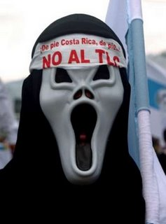 A Costa Rican man wears a mask with the words 'No TLC' (No Free Trade Agreement) during a protest march near the National Stadium where President Oscar Arias is holding his inauguration ceremony, in San Jose, Costa Rica May 8, 2006. Nobel laureate Arias begins a second stint as president of Costa Rica today, taking power in a nation divided over free trade with the United States and widely seen as rudderless. Arias, is the 53nd president of Costa Rica, dating from 1848. REUTERS/Oswaldo Rivas