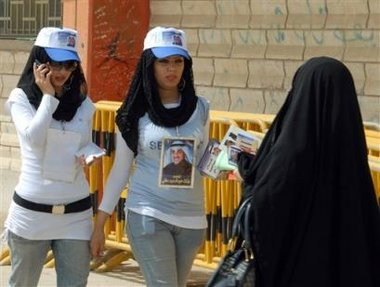 a kuwaiti woman voter right and two young camapign volunteers walk by at a polling station in. Black Bedroom Furniture Sets. Home Design Ideas