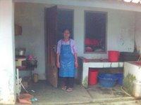 Ceu Ana di dapur asrama dengan baju dinasnya